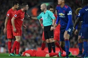 Liverpool's English midfielder Jordan Henderson (2nd L) talks to referee Anthony Taylor as Liverpool's English midfielder James Milner lies injured during the English Premier League football match between Liverpool and Manchester United at Anfield in Liverpool, north west England on October 17, 2016. / AFP PHOTO / Paul ELLIS / RESTRICTED TO EDITORIAL USE. No use with unauthorized audio, video, data, fixture lists, club/league logos or 'live' services. Online in-match use limited to 75 images, no video emulation. No use in betting, games or single club/league/player publications. /